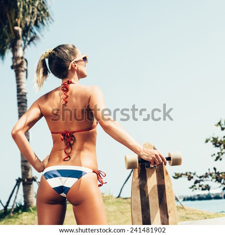 Young sporty girl skateboarder posing with longboard. Woman looking away . Outdoor lifestyle - stock photo