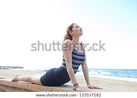 Young sporty hispanic woman doing yoga and stretching her back while on a beach against a blue sky. - stock photo