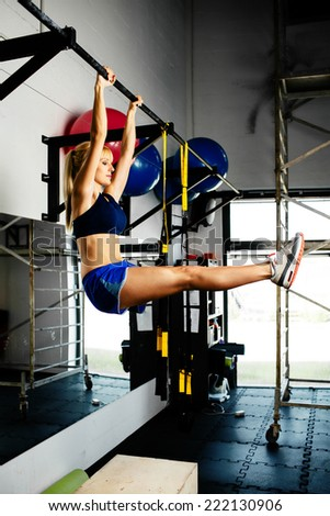 Young sporty woman doing pull-ups in a gym - stock photo