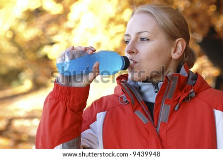 Young, sporty woman drinking isotonic in the park - stock photo
