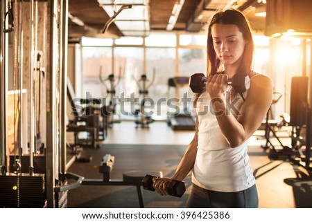 Young sporty woman lifting steel dumbbell. - stock photo