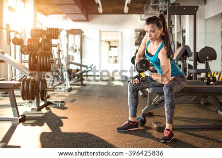Young sporty woman lifting steel dumbbell in gym. - stock photo