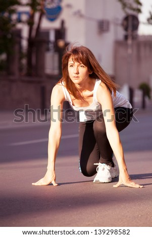 Young sporty woman preparing to run dressed up in a gym suit - stock photo