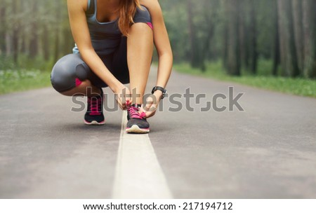 young sporty woman preparing to run in early foggy morning in the beautiful nature forest, wellness concept - stock photo