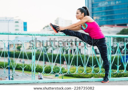 Young sporty woman stretching her leg on railing and listening to personal stereo  - stock photo
