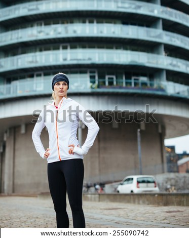 Young sporty woman taking a break after workout outdoors. Caucasian female athlete on street looking away. - stock photo