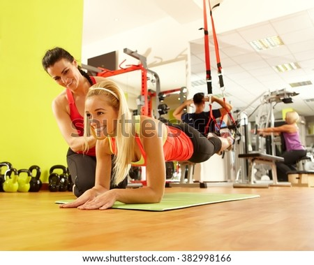 Young sporty woman training in gym with personal trainer. - stock photo