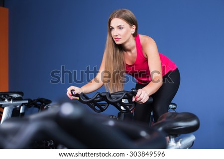 Young sporty woman, with long dark hair, wearing in sportswear, doing exercise on bicycle in the gym centre, on the blue wall background, waist up - stock photo