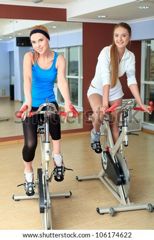 Young sporty women doing exercises on bicycles in the gym centre.
