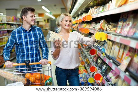 Young spouses buying cheddar in cheese section of supermarket - stock photo
