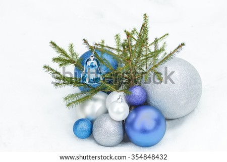 Young spruce tree on snowy ground with Christmas silver and blue ornaments at the bottom - stock photo
