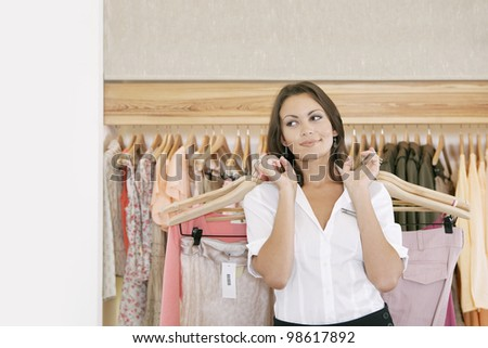 Young store attendant holding hangers with clothes in a fashion store.