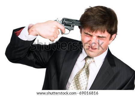 Young Stressed businessman in suit with gun making suicide - stock photo