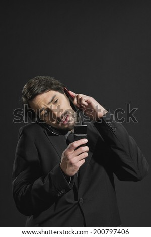 Young stressed businessman using two mobile phones - stock photo