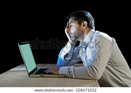 young stressed businessman working with computer laptop in frustration, depression, work stress problems and despair concept isolated on black background - stock photo