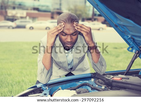 young stressed man having trouble with his broken car looking in frustration on failed engine  - stock photo
