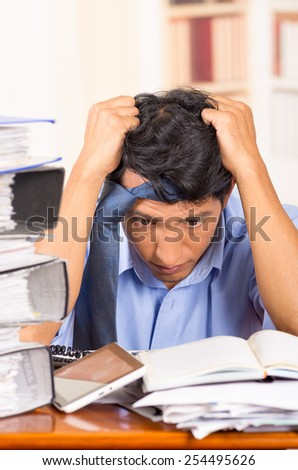 young stressed overwhelmed business man with piles of folders on his desk with tie on his head - stock photo