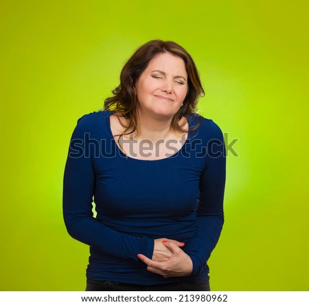 Young stressed woman having stomach pain, hands on belly, having bad aches, pains, isolated green background. Food poisoning, influenza, cramps. Negative emotions, facial expressions, feelings - stock photo