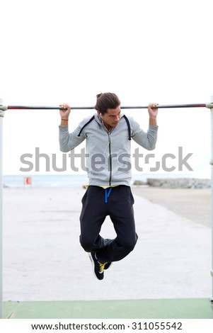 Young strong athlete doing pull up exercise outdoors at street gym and listening to music in headphones, male runner working out on horizontal bar in cloudy day, sportsman do physical exercises  - stock photo