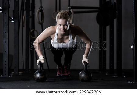 Young strong girl doing push-ups na kettlebells - stock photo