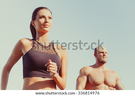 Young strong male and female  fitness models outdoors in beautiful landscape. Man and woman running in park close up - stock photo