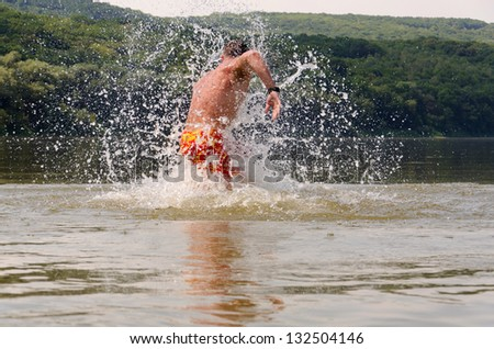 young strong man cavorting in the water