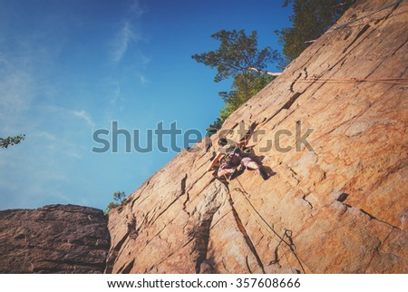 Young strong man climbs on a yellow cliff to the blue sky