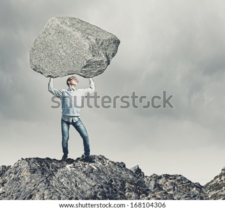 Young strong man holding huge stone above head - stock photo