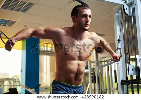 Young strong man with torso is doing flys on cable crossover in gym - stock photo