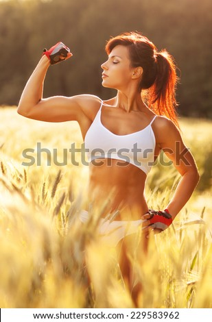Young strong sports woman standing at summer field with high grass and looking on her hands muscles. Red sunset light. - stock photo