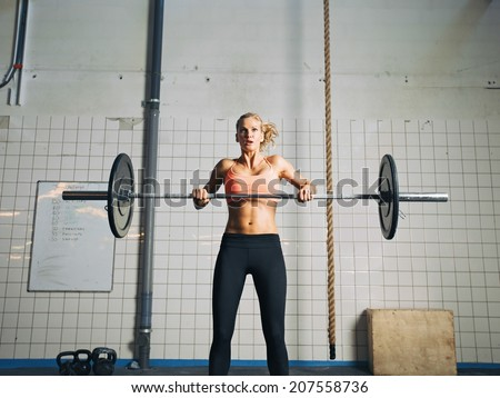 Young strong woman practices cross fit in a gym. Fit female holding a barbell with weights for crossfit. - stock photo