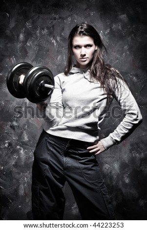 Young strong woman sport exercises. Contrast colors.