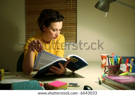 Young student at a desk preparing for an exam - stock photo