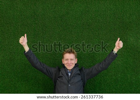 young student at a green wall shows his hand