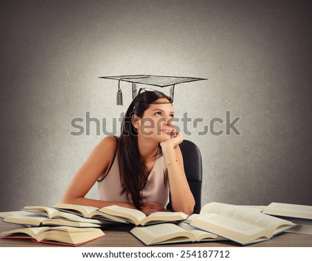 Young student between books dreams the graduation - stock photo