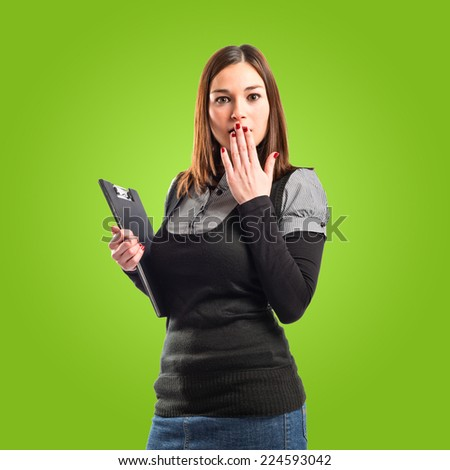 Young student doing surprise gesture over green background  - stock photo