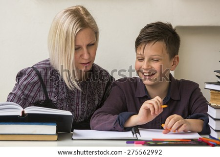 Young student engaged in the lessons with his teacher. - stock photo