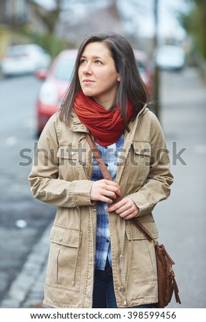 Young student female walk on the side of the street, autumn or spring clothes, blurred street as background - stock photo