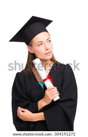 Young student girl dressed in black graduation gown. Isolated on white background. Girl holding diploma