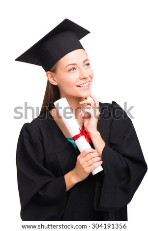 Young student girl dressed in black graduation gown. Isolated on white background. Girl holding diploma and looking aside