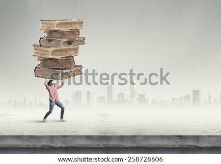 Young student girl lifting pile of old books above head - stock photo