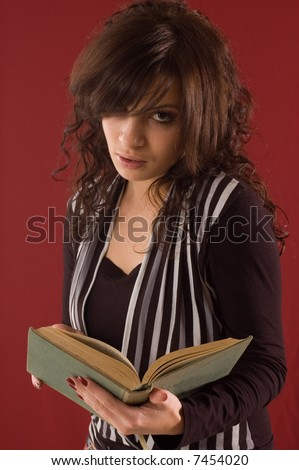 Young student girl with books on red backgrounds