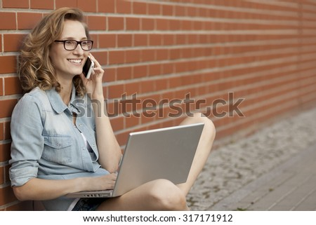 Young student having good time using phone while working outside with laptop - stock photo