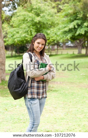 Young student holding textbook while posing in a park - stock photo