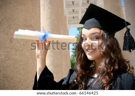 Young student in gown near the university with diploma - stock photo