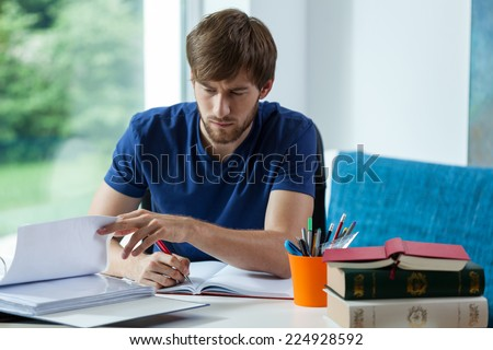 Young student learning and spending time behind the desk - stock photo
