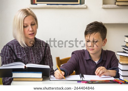 Young student learns at home with a his mom tutor. - stock photo