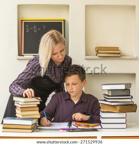Young student learns at home with a his tutor. - stock photo