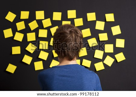 Young student looking to a board full of yellow notes - stock photo