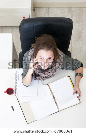 Young student, looking up, during exam preparations, studying the notes on her desk in her dorm room - stock photo